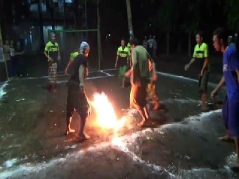 Trẻ em Indonesia chân trần đá bóng lửa trong đêm